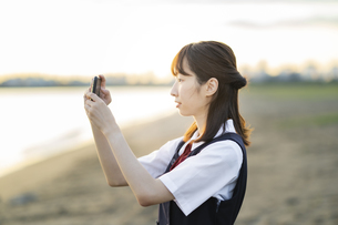 スマートフォンで景色を撮影するアジア人女性の高校生の写真素材 [FYI04863841]
