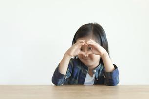手でハートを作って覗く女の子の写真素材 [FYI04863861]