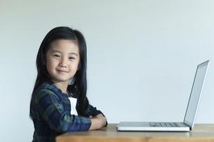 ノートパソコンの前でカメラを見る女の子の写真素材 [FYI04863922]