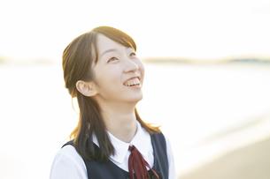 夕陽に包まれるアジア人女性の高校生の写真素材 [FYI04864097]