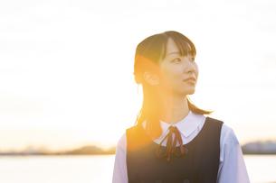 夕陽に包まれるアジア人女性の高校生の写真素材 [FYI04864113]