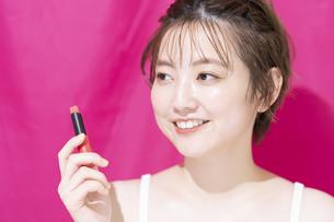 口紅を持つアジア人の若い女性の写真素材 [FYI04864150]