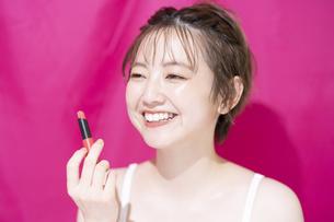 口紅を持つアジア人の若い女性の写真素材 [FYI04864151]