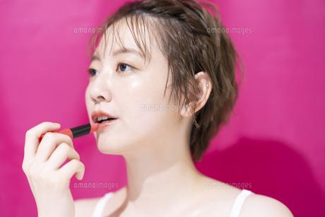 口紅を塗るアジア人の若い女性の写真素材 [FYI04864152]
