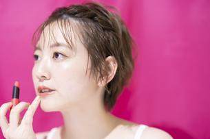 口紅を塗るアジア人の若い女性の写真素材 [FYI04864153]