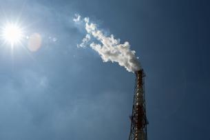 煙を吹き上げる煙突と太陽の写真素材 [FYI04864278]