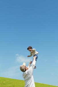 草原で高い高いをする親子の写真素材 [FYI04864281]