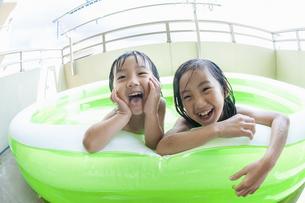 ベランダのプールで遊ぶ姉弟の写真素材 [FYI04864296]