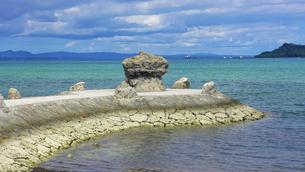 沖縄本島、海中道路の展望台近くにある「象の鼻」の様に湾曲した琉球石灰岩で造られた堤防の写真素材 [FYI04864805]