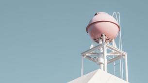【生活】青空の下のピンク色の屋上の貯水槽 貯水タンクの写真素材 [FYI04864815]