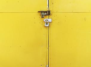 施錠された黄色い倉庫のドアの写真素材 [FYI04865221]