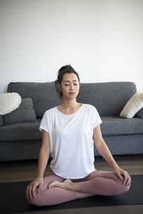 室内で瞑想をしている女性の写真素材 [FYI04865342]