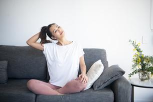 ソファで首をストレッチしている女性の写真素材 [FYI04865351]