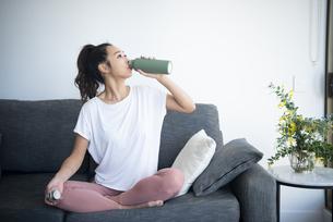 ソファで水分補給をしている女性の写真素材 [FYI04865353]