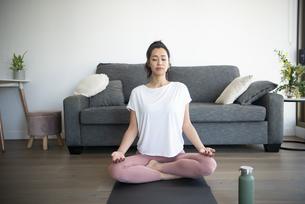ヨガマットの上で瞑想をしている女性の写真素材 [FYI04865370]