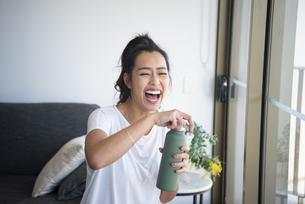 ウォーターボトルを持って笑っている女性の写真素材 [FYI04865378]
