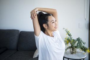 室内でストレッチをしながら笑っている女性の写真素材 [FYI04865381]