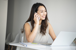 パソコンを開いて電話をしている女性の写真素材 [FYI04865403]