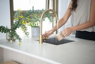 アイランドキッチンでカップを洗っている女性の写真素材 [FYI04865466]