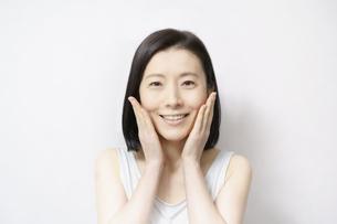 顔を触る日本人女性(40-50代のイメージ)の写真素材 [FYI04865500]