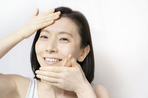 顔を触る日本人女性(40-50代のイメージ)の写真素材 [FYI04865505]