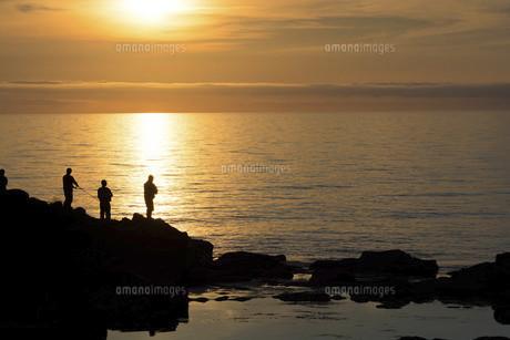美しい夕暮れの海と釣り人のシルエットの写真素材 [FYI04865790]