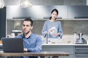 ダイニングテーブルで仕事をする男性と、キッチンで皿洗いをする女性の写真素材 [FYI04866172]