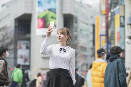 日本・東京・渋谷で写真を撮り歩く女性の写真素材 [FYI04866173]