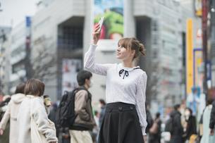 日本・東京・渋谷で写真を撮り歩く女性の写真素材 [FYI04866174]