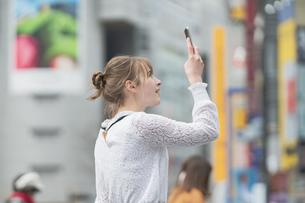 日本・東京・渋谷で写真を撮り歩く女性の写真素材 [FYI04866175]