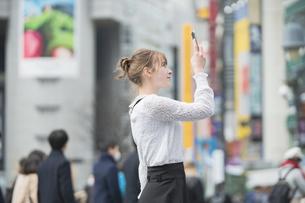 日本・東京・渋谷で写真を撮り歩く女性の写真素材 [FYI04866176]