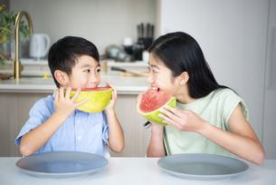 向かい合って大きなカットすいかを食べている兄弟の写真素材 [FYI04866888]