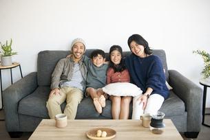 ソファでくつろいでいる4人家族の写真素材 [FYI04866910]