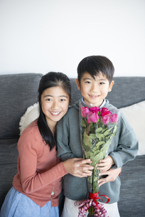 薔薇の花束を持っている男の子と女の子の写真素材 [FYI04866912]