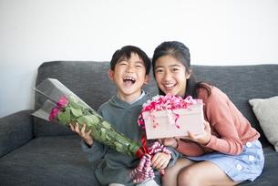 薔薇の花束とプレゼント持って笑っている男の子と女の子の写真素材 [FYI04866915]