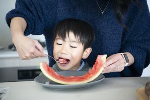 スイカを食べさせてもらっている男の子の写真素材 [FYI04866919]