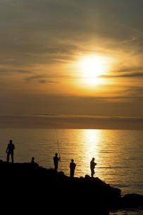 美しい夕暮れの海と釣り人のシルエットの写真素材 [FYI04867417]