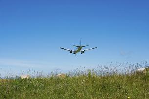 着陸するジェット旅客機と牧草畑の写真素材 [FYI04867425]
