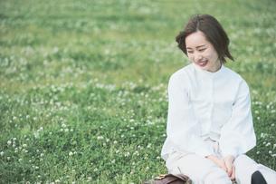 芝生でくつろぐ女性の写真素材 [FYI04867793]