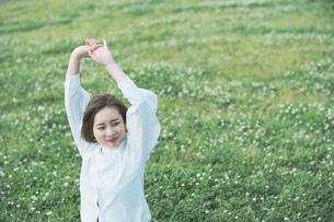 芝生でくつろぐ女性の写真素材 [FYI04867797]