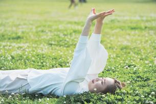 芝生でくつろぐ女性の写真素材 [FYI04867801]
