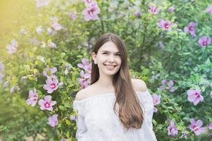 緑の前で笑顔を見せる女性の写真素材 [FYI04867810]