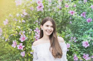 緑の前で笑顔を見せる女性の写真素材 [FYI04867811]