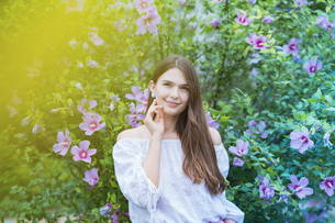 緑の前で笑顔を見せる女性の写真素材 [FYI04867812]