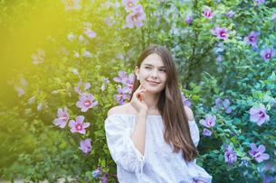 緑の前で笑顔を見せる女性の写真素材 [FYI04867813]