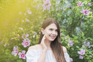 緑の前で笑顔を見せる女性の写真素材 [FYI04867814]