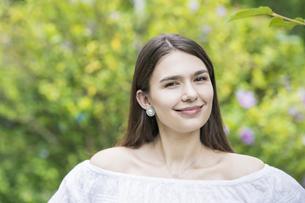 緑の前で笑顔を見せる女性の写真素材 [FYI04867816]