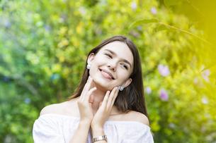 緑の前で笑顔を見せる女性の写真素材 [FYI04867822]
