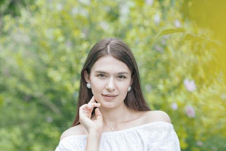 緑の前で笑顔を見せる女性の写真素材 [FYI04867823]