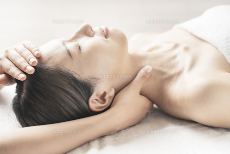 エステサロンで頭と首をマッサージされる若い女性の写真素材 [FYI04867826]